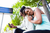 African couple waiting at bus station — Stock Photo