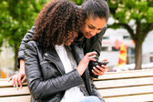 Friends chatting with smartphone on park bench — Stock Photo