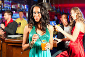 People with cocktails in bar or club — Stock Photo