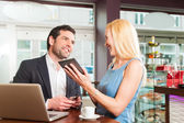 Working colleagues - a man and a woman - sitting in cafe — Stock Photo