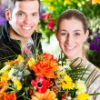 Female florist and male customer in flower shop — Stock Photo #79328970