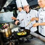 Asian Chefs in restaurant kitchen cooking — Stock Photo #79329500