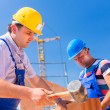 Construction site workers building walls on house — Stock Photo #79331692