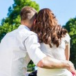 Couple in love sitting on park lawn — Stock Photo #79334730
