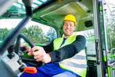 Builder driving construction machinery — Stock Photo