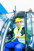 Driver driving construction excavator — Stock Photo