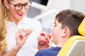 Female Orthodontist explaining boy braces — Stock Photo