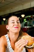 Woman in a restaurant eating hamburger — Stock Photo