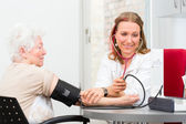 Doctor measuring blood pressure of senior patient — Stock Photo