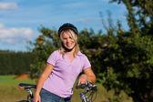 Mujer con bicicleta y casco — Foto de Stock