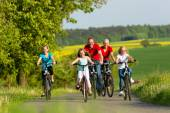 Family with kids cycling in summer with bicycles — Stock Photo