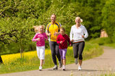Family running in the meadow for sport — Stock Photo