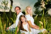 Happy family sitting in meadow — Stock Photo