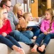 Family reading story in book on sofa in home — Stock Photo #79442054