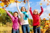 Friends romping in harvest leaves throwing foliage — Stock Photo