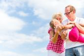 Family romping on field — Stock Photo