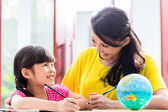 Chinese mother doing school homework with child — Stock Photo