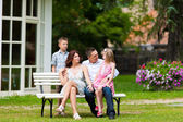 Family sitting in front of their home — Stock Photo