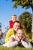 Familie met fiets in park in de herfst — Stockfoto