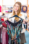 Woman choosing clothes in fashion shop — Stock Photo
