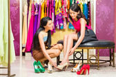 Asian sales lady in shop offering shoes — Stock Photo