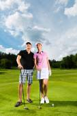 Young sportive couple playing golf on a course — Stock Photo