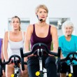 Senior people in gym spinning on fitness bike — Stockfoto #79809192