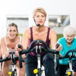 Senior people in gym spinning on fitness bike — Stockfoto #79809214