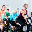 Senior people in gym spinning on fitness bike — Stockfoto #79809370