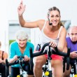 Senior people in gym spinning on fitness bike — Stockfoto #79809390