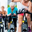 Senior people in gym spinning on fitness bike — Stockfoto #79809394