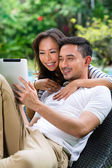 Asian couple outdoor with a tablet pc — Stock Photo
