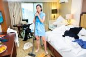 Chambermaid cleaning in Asian hotel room — Stock Photo