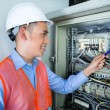 Asian Electrician at panel on construction site — Stock Photo #82331146