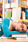 Student in library asleep over books — Stock Photo
