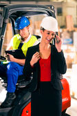 Forklift driver and supervisor at warehouse — Stock Photo