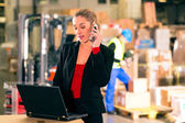 Dispatcher using phone at warehouse of forwarding — Stock Photo