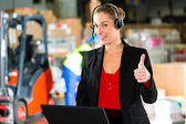 Dispatcher using headset at warehouse of forwarding — Stock Photo