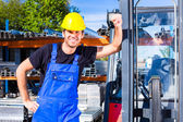 Builder with site pallet transporter or lift fork truck — Stock Photo