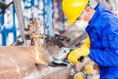 Metal worker in factory grinding metal of pipeline — Stock Photo