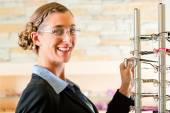 Young woman at optician with glasses — Stock Photo