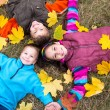 Three kids on yellow leaves — Stock Photo #54934673