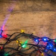 Christmas lights on wooden background — Stock Photo #60071555