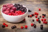 Frozen berries in plate on wooden background — Zdjęcie stockowe