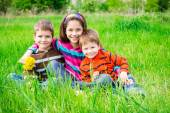 Three smiling kids on green meadow — Stock Photo