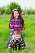 Two kids playing on green grass — Stock Photo