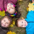 Three kids on yellow leaves — Stock Photo #80777170