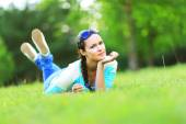 Young pretty woman lying on the grass at summer sunset — ストック写真