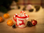 Insulated wool cloth mug with embroidered deer on the wooden table mug with tangerines and a candy — Stock Photo