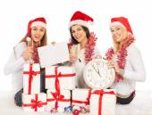 Three beautiful girls on the New Year's Eve sit with clock, gifts, champagne — Stock Photo